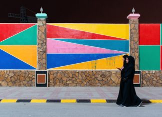 Two women walk past a brightly painted wall near the entrance of the Khareef Festival in Salalah, Oman. Photo by Isaac D. Pacheco