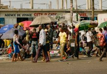 Pedestrians walk along the notoriously congested highway linking Kinshasa's city center to N'djili International Airport. Photo by Isaac D. Pacheco
