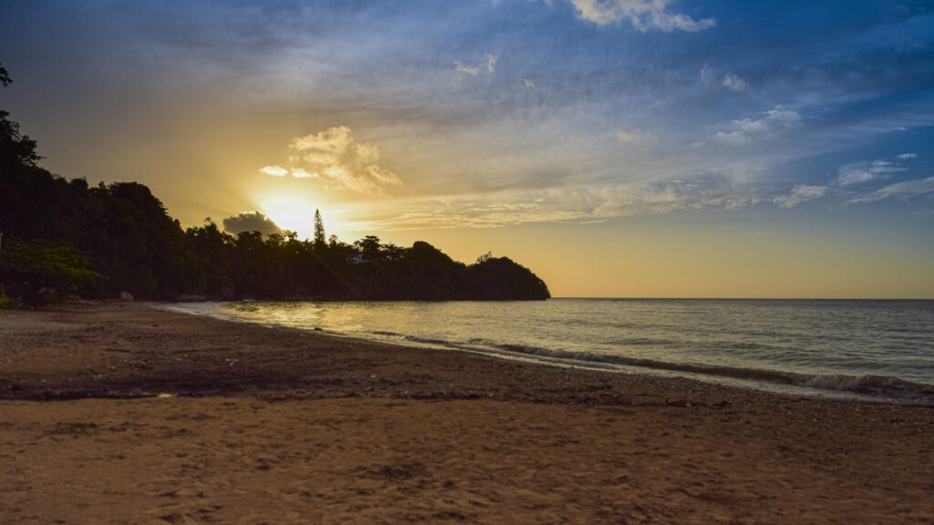 The sun falls beyond the trees for a picturesque sunset at Oracabessa Beach. Photo by Katherine Judd