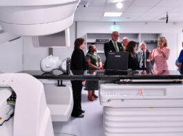 U.S. Ambassador Jackie Wolcott (center right, hands raised) receives a tour of the LINAC (linear accelerator) facility at the International Atomic Energy Agency's (IAEA's) laboratories in Seibersdorf, Austria, together with other Vienna-based ambassadors, June 2019. Photo by Dean Calma
