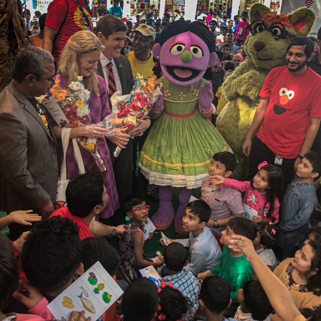 """Ambassador Earl Miller (third from left) watches as children meet their favorite """"Sisimpur"""" characters from the Bangladeshi version of the popular children's television series """"Sesame Street."""" Photo courtesy of Embassy Dhaka"""