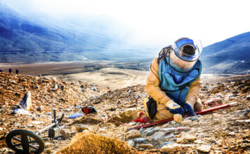 A Danish Demining Group deminer carefully extracts a landmine from the side of the mountain in Afghanistan. Photo courtesy of the Danish Demining Group
